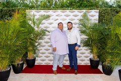 Gus and Joander smile together at camera, while standing on red carpet in front of decorative logo banner